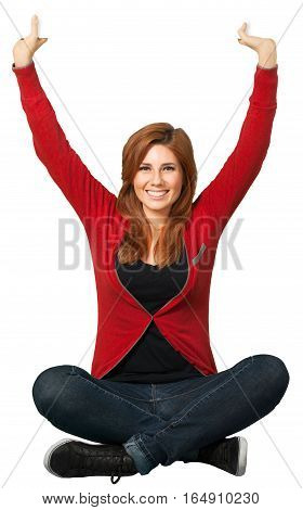 Redheaded woman sitting cross legged with her arms in the air