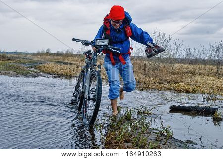 Mullashi, Russia - April 29, 2007: Bicycle tourist goes along the road flooded. Trip to Duvan river. Tyumen region