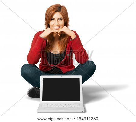 Red headed woman sitting crosslegged with an open laptop in front of her