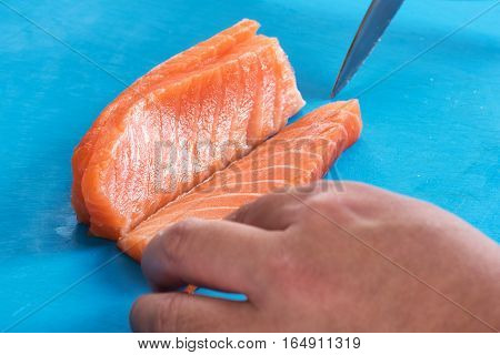 Close up of cooks hands slicing fresh salmon fillet lengthwise on blue surface
