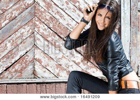 Sexy fashionable woman near the wall