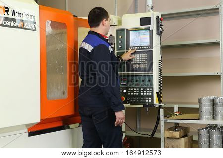 St. Petersburg Russia - September 3 2015: The operator controls the CNC milling machines using control panel with display.