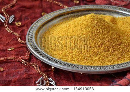 Turmeric powder over an indian patchwork carpet