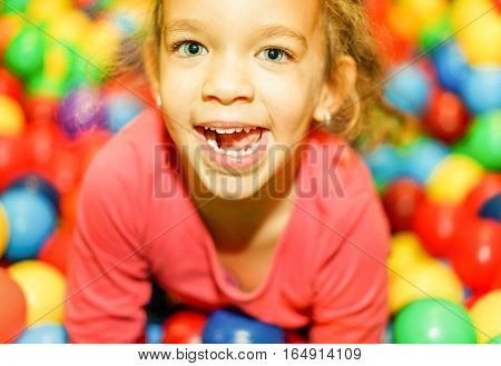 Pretty mixed race female child having fun in children playground indoor - Portrait of little happy girl playing in kindergarten - Childhood and youth concept - Focus on eyes - Warm vivid filter