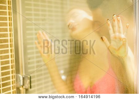 Reflection view of young couple having love sex inside shower box with vapor inside - Young people doing foreplay - Sexual and romance concept - Soft focus on girl left fingers hand - Warm filter