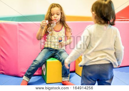 Two little female children blowing soap bubbles in playground nursery school - Young people having fun indoor - Friendship and game concept - Focus on left child face - Warm vivid filter