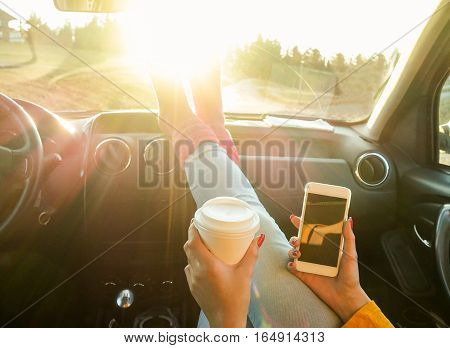 Woman toasting coffee take away go cup and using smart phone inside car with feet in warm socks on dashboard - Travel and trend concept - Focus on paper cup hand - Warm filter with original sun light