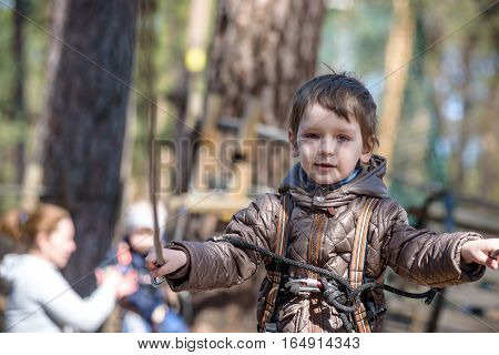 Cute child boy climbing in a rope playground structure