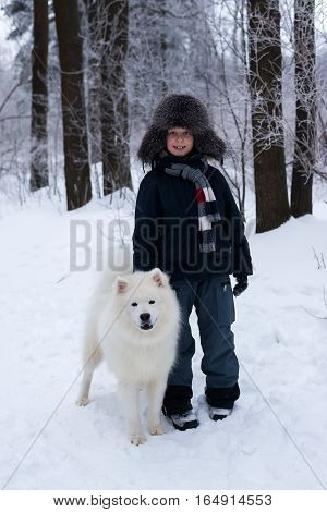 The boy in the hat standing next to a dog