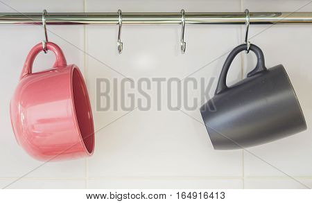 Two hanging mugs, one pink and one gray