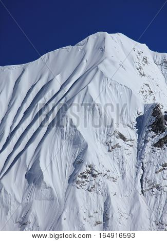 Snow covered mountain next to mount Nuptse. Scene in the Himalayas.