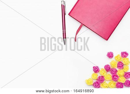 pink diary with a pen and small yellow pink roses on a white background business minimal concept for women. Flat lay top view.