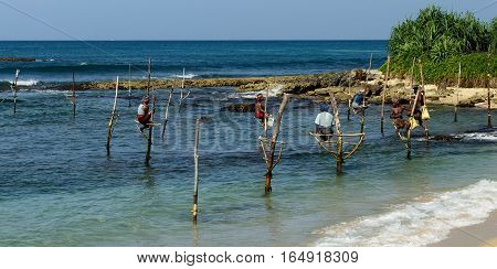 GALLE SRI LANKA - MARCH 02:Fishermen on stilts trying to catch a fish on the pole on the coast of Sri Lanka. Galle on March 02 2015