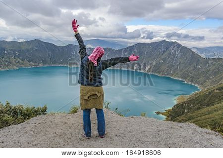 Young woman with hands up at watching the view at Quilotoa lake Latacunga Ecuador