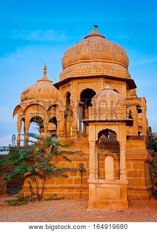 The royal cenotaphs of historic rulers also known as Jaisalmer Chhatris at Bada Bagh in Jaisalmer Rajasthan India. Cenotaphs made of yellow sandstone at sunset