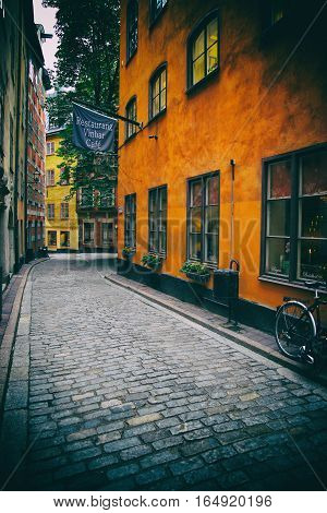 STOCKHOLM SWEDEN - AUGUST 19 2016: View of old narrow Kindstugatan street and colorful buildings in Gamla Stan Gamla Stan is old town in central Stockholm Sweden on August 19 2016.