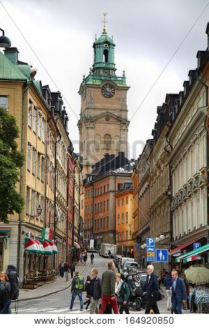 STOCKHOLM SWEDEN - AUGUST 19 2016: View on Church of St. Nicholas (Storkyrkan) and beautiful street Storkyrkobrinken (Gamla Stan) with pedestrian walk in Stockholm Sweden on August 19 2016.