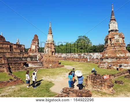 AYUTTHAYA THAILAND - NOVEMBER 29: Unidentified tourists visit Wat Mahathat in the Ayutthaya Historical Park on November 29 2016 in Ayutthaya Thailand