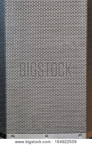 Gray music speaker standing upright with a metal grid, close-up