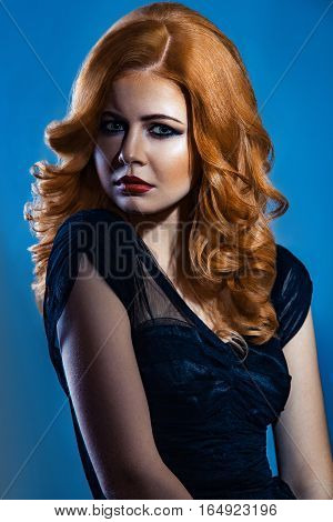 Beautiful fashion girl with long wavy red brown hair. fair-haired model with curly hairstyle and fashionable smoky makeup . studio shot on dark blue background.