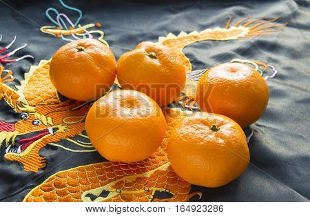 Chinese New year, mandarins in silk fabric with embroidered dragon.