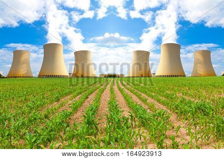 Thermal power plant with corn field, cloudy sky