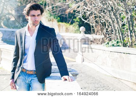 Elegant beautiful business pensive man. A handsome young man outdoors. Stylish hair and intense beauty. Jacket with white shirt. Intense sun.
