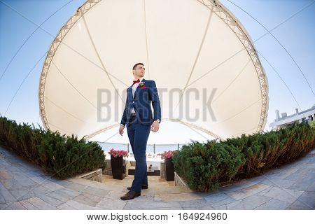 Portait of a young handsome man in suite on the nature. Gorgeous groom, outdoors