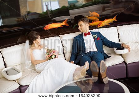 Wedding couple in love. Beautiful bride in white dress with brides bouquet and handsome groom dressed blue suit sitting in cafe at big aquarium with goldfishes. Concept of wedding celebration or vacation
