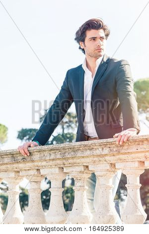 Elegant beautiful business pensive italian man leaning on a old balcony. The young man wearing elegant clothes with a white shirt and dark suit. Bright daylight.