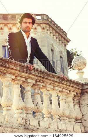 Handsome and attractive young man outdoors, leaning on balcony, looking sensuous and thoughtful attitude. The young man wearing elegant clothes with a white shirt and dark suit. Bright daylight.
