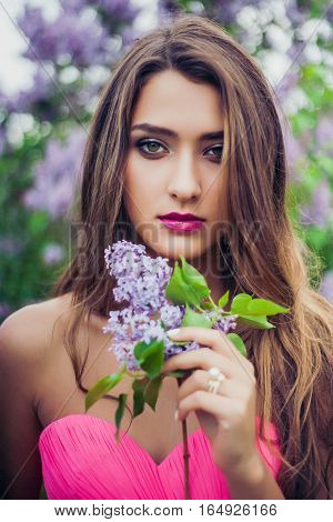 Portrait of young beautiful woman holding a lilac branch. Professional make-up and hairstyle. Perfect skin. Fashion photo. Natural beauty.