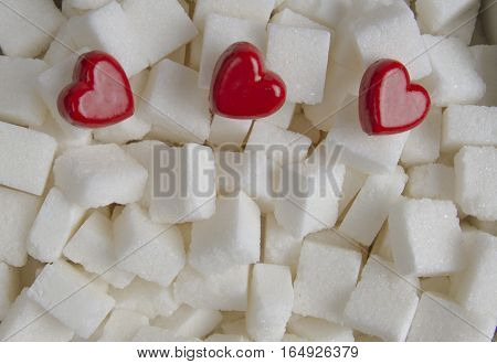 Sugar cubes with three red hearts as background. Close up. Top view