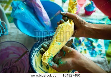 Close up of hands holding pastry bag full of bright yellow cream