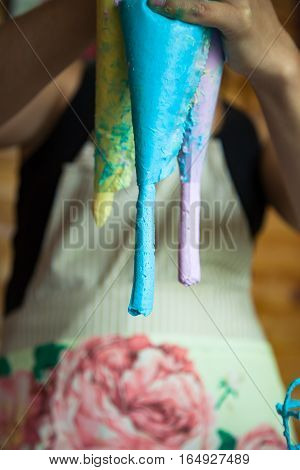 Close up of unrecognizable chef squeezing colorful cream from a pastry bags
