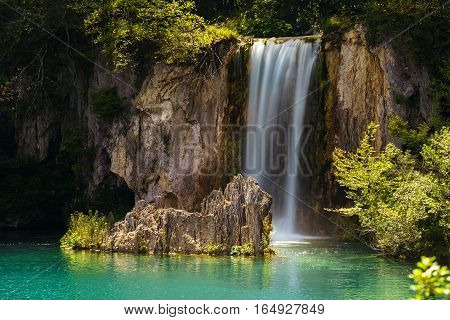 Waterfall and a lake with a stone in the Plitvice Lakes National Park.