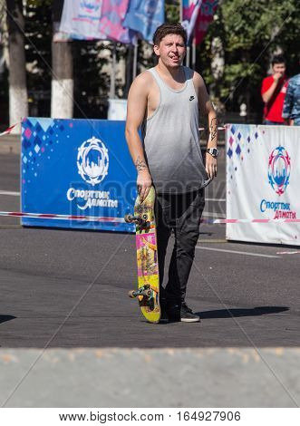 KAZAKHSTAN ALMATY - AUGUST 28, 2016: Urban extreme competition, where the city athletes compete in the disciplines: skateboard, roller skates, BMX. Skateboarder doing a trick in skate park.
