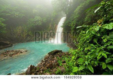 Rio celeste waterfall at foggy day Tenorio national park Costa Rica