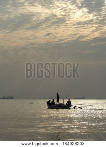 Four people in a boat against the setting sun on the ocean
