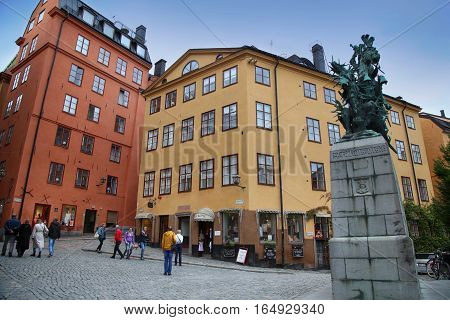 STOCKHOLM SWEDEN - AUGUST 19 2016: Tourists walk and Statue of Sankt Goran & the Dragon located on the Kopmanbrinken street Gamla stan in Stockholm Sweden on August 19 2016.