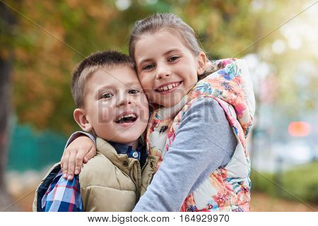 Portrait of a smiling little brother and sister hugging while enjoying a day outside together in a park in the autumn
