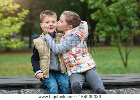 Cute little girl kissing her smiling little brother on the cheek while sitting together on a bench in a park in the autumn