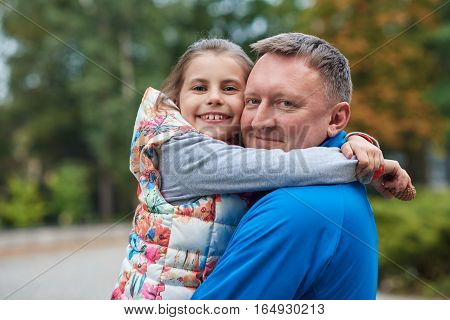 Portrait of a smiling father and daughter hugging while enjoying a day outside together in a park in the autumn