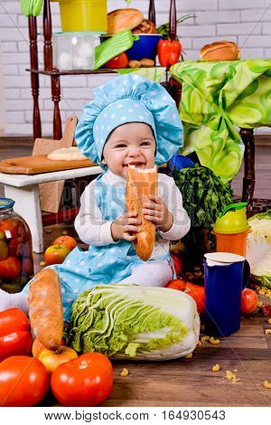 little girl in the cook clothes with loaf of bread in the kitchen