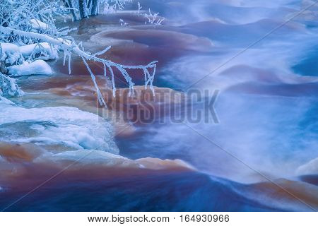 Frozen branch in cold winter stream landscape