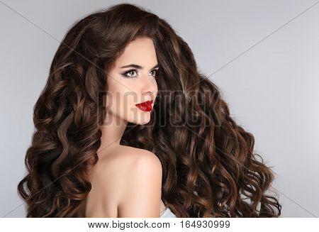 Brunette. Long Hair. Curly Hairstyle. Beautiful Woman With Wavy Healthy Hair And Red Lips Makeup Iso