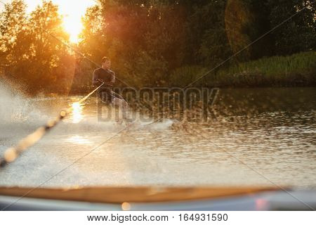 Man riding wakeboard on wave of motorboat in lake at sunset. Male athlete in action water skiing on lake.