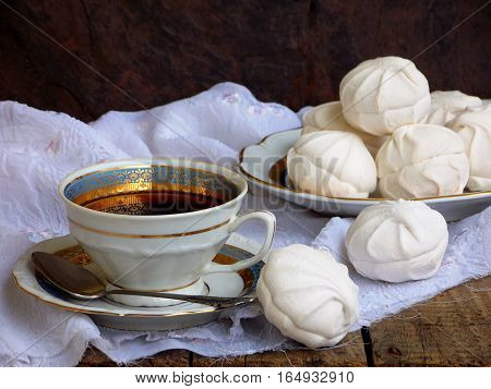 Sweet White Russian Marshmallow, Chocolate Zephyr, Meringue And Cup Of Coffee On Wooden Background.