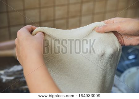 Cook holding a yeast dough in the kitchen
