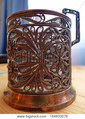 Cup holder. Cupronickel, tracery pattern. Closeup. Retro.
